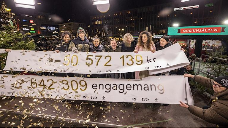 Bild från torget i Västerås, på scenen. Där står programledarna, ambassadörerna och Kodjo. De håller i pappersrullar där man ser siffrorna på hur mycket som samlats in och hur många engagemang.