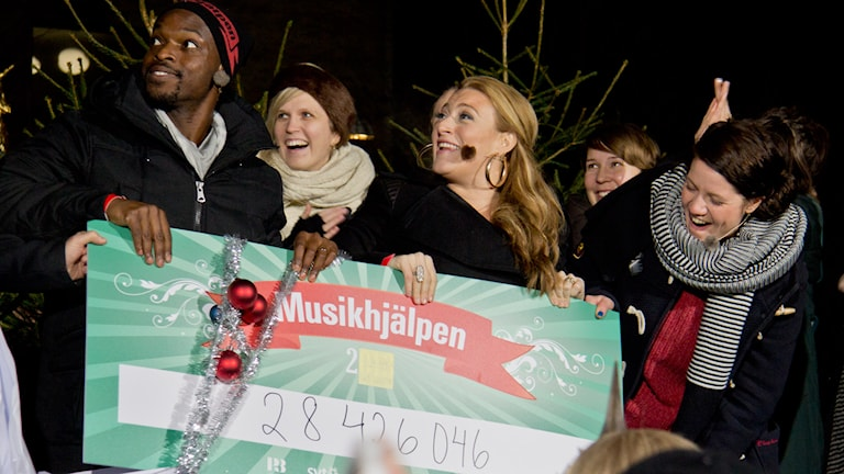 Kodjo, Sarah och Emma visar upp hur mycket pengar Musikhjälpen 2013 dragit in. Foto: Eric Tapper/Sveriges Radio