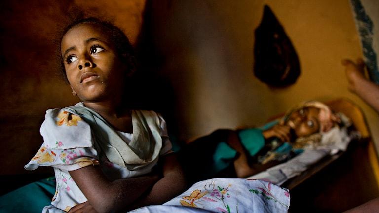 Sexårig dotter med sin aidssjuka mamma i bakgrunden. Mamman är 20 år. Bild: Mikkel Østergaard/TT