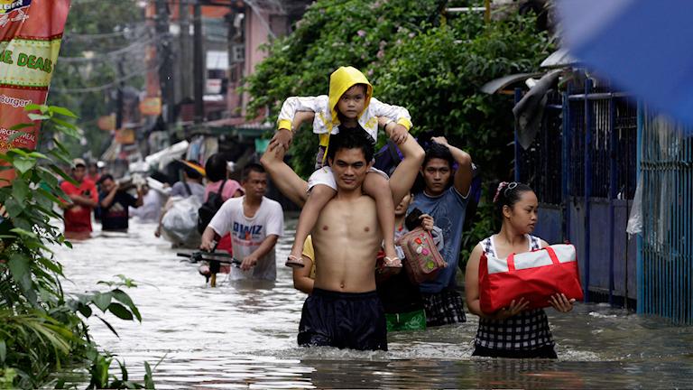 Familjer lämnar sina hem för att söka skydd på högre höjd undan översvämningarna i Pasig City, en förort till Filippinska huvudstaden Manilla. Foto: Pat Roque/AP/TT