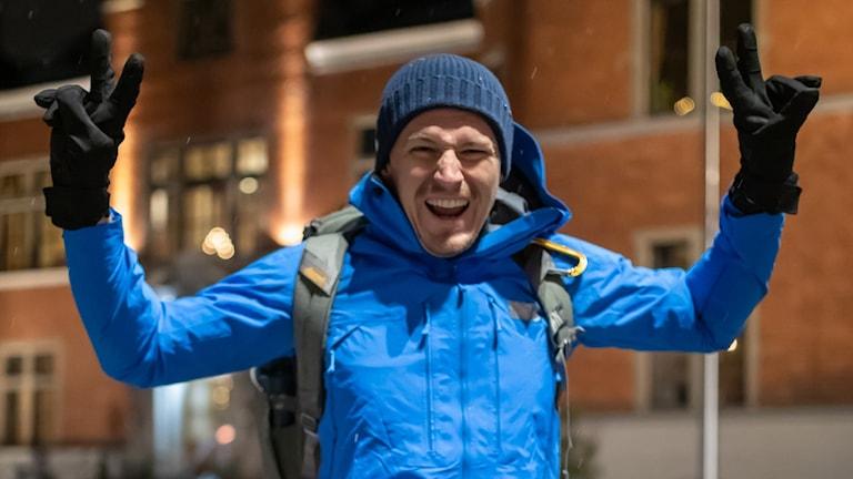 En man i blå jacka och mössa höjer triumferande armarna över huvudet med ett brett leende över hela ansiktet. Han har svarta vantar och grön ryggsäck på ryggen.