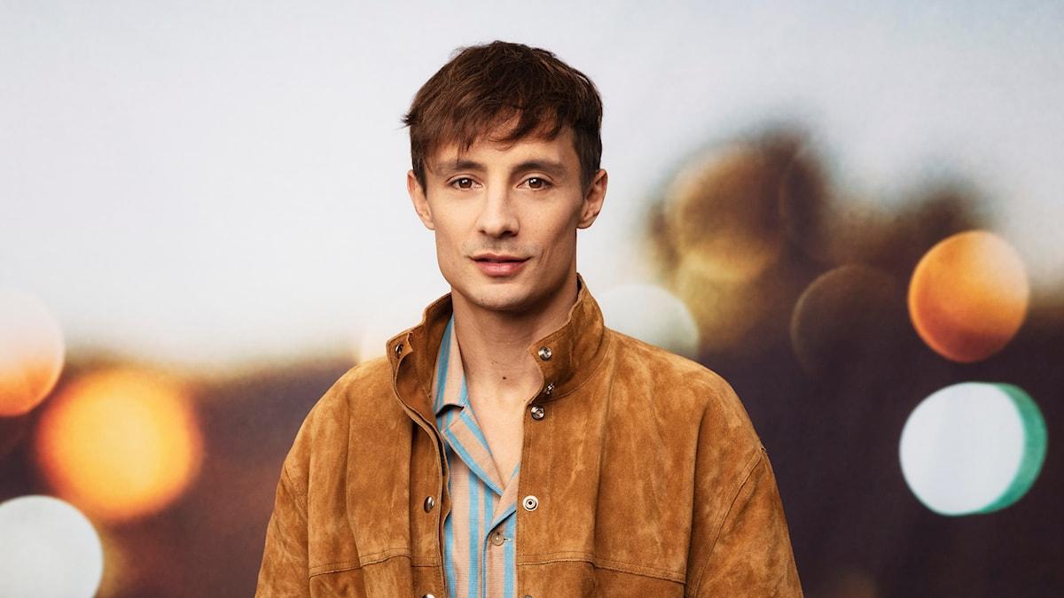Fotot föreställer en man med brunt hår, blågulrandig skjorta och ljusbrun mockajacka. han står i mitten av bilden och tittar rakt in i kameran.