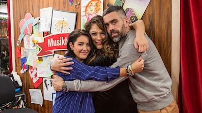 Foto på Molly Sandén, Farah Abadi och Kalle Zackari Wahlström som tittar in i kameran och kramar om varandra sista dagen i Musikhjälpenburen 2017.