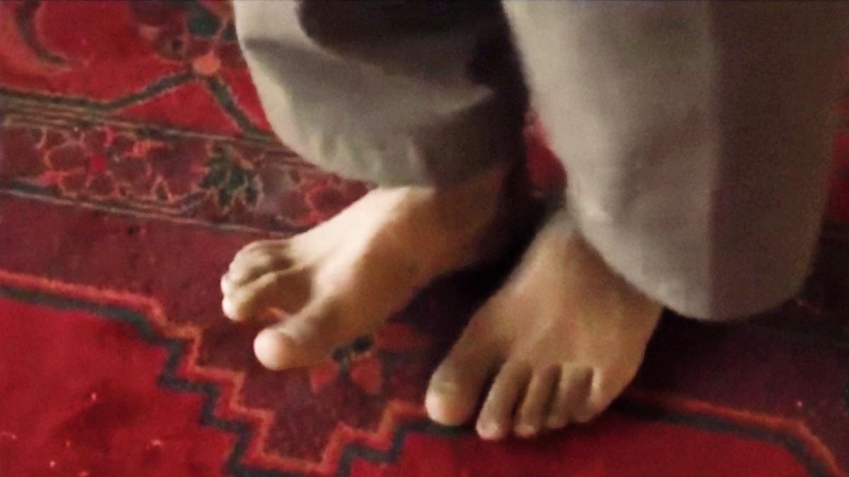 En pojkes bara fötter mot en röd matta.