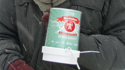 Person i svart jacka håller i en insamlingsbössa för Musikhjälpen