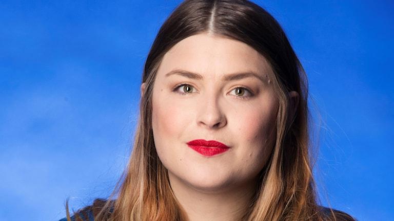 Närbild på Linnea Henriksson mot blå bagrund