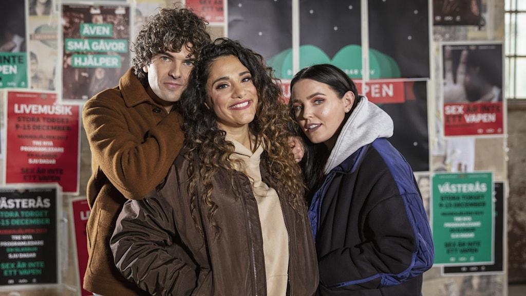 En bild på Daniel, Farah och Miriam framför en väg med musikhjälpen-bilder. Daniel och Miriam lutar sig lite på Farah. Alla tre ser glada ut.