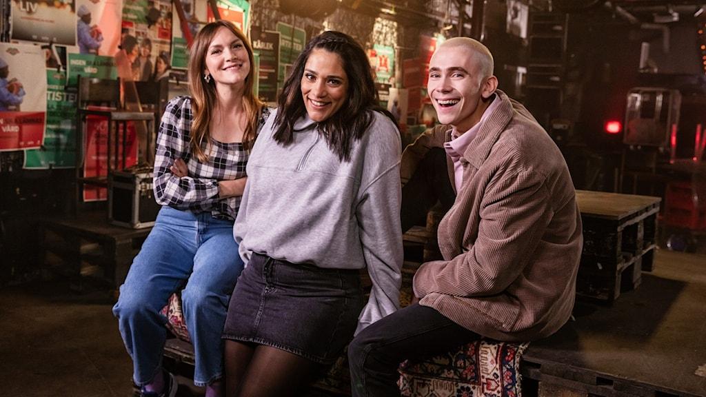Brita Zackari, Farah Abadi och Felix Sandman står i en dovt upplyst lokal- det ser ut som en konsertlokal utan folk. På väggarna sitter Musikhjälpenaffischer. De står lutade mot ett bort och tittar in i kameran och ler.