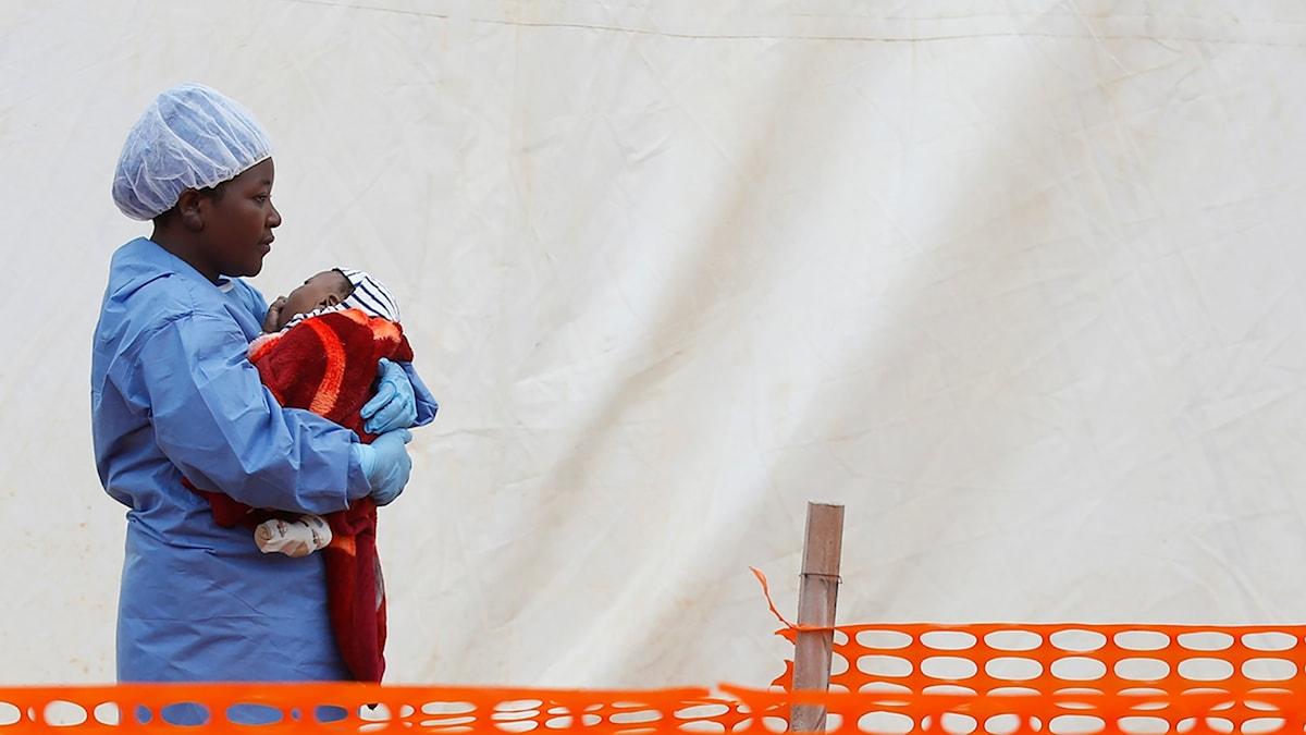 En bild på en kvinna i sjukvårdskläder som håller ett litet barn i famnen. Hon står utanför ett tält.