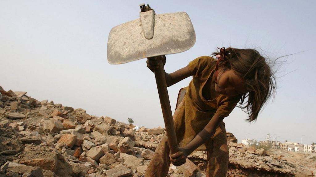 Bilden visar en flicka som arbetar. Hon håller i en hacka och står böjd framåt över en stenig backe.