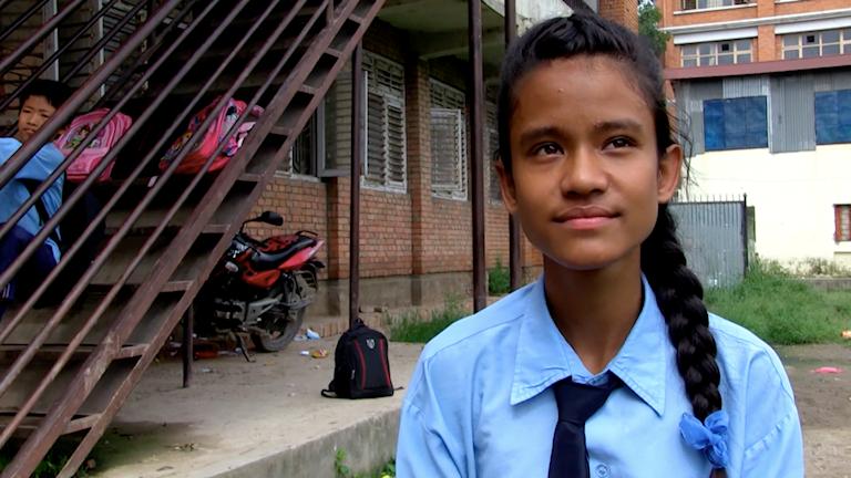 På fotot syns en flicka med en fläta i ljusblå skoluniformsskjorta. Bakom henne ser du en trappa där en skolkamrat sitter.