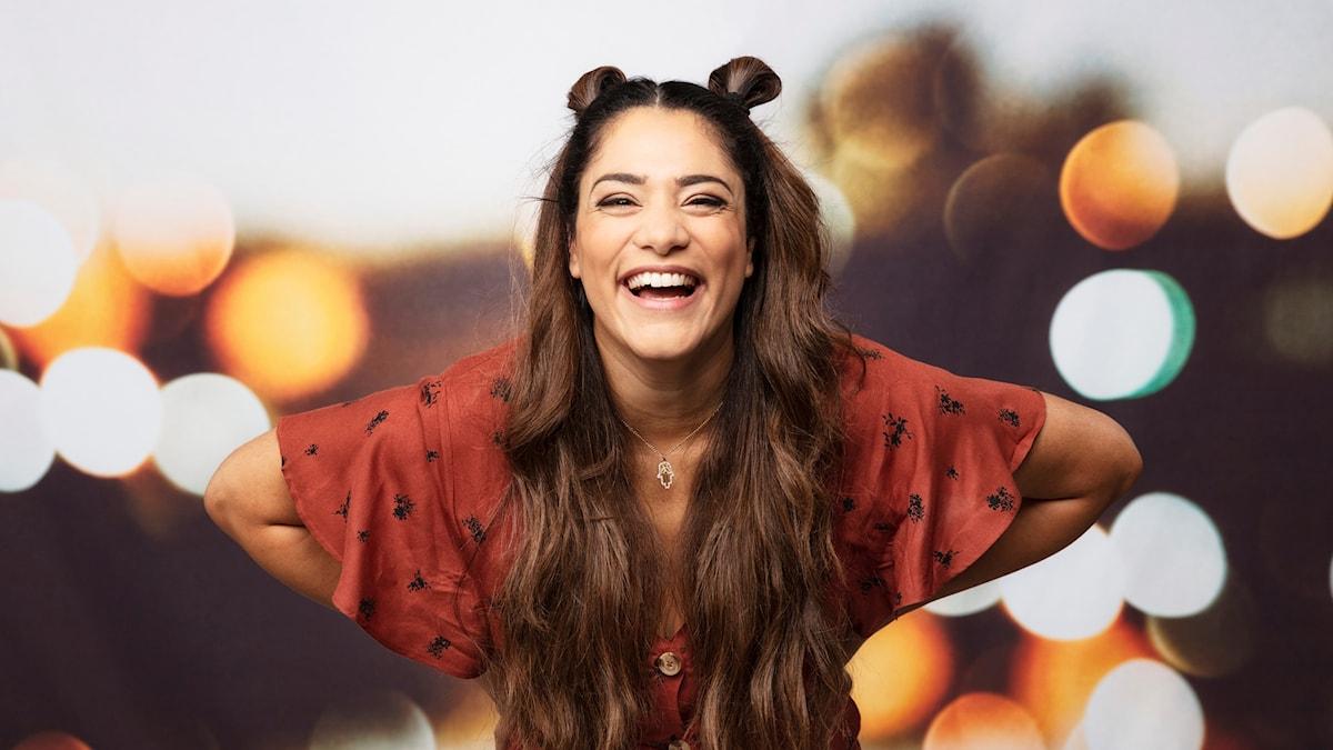 Fotot föreställer en framåtlutande skrattande kvinna i brun klänning med händerna på höfterna. Hon har den långa bruna håret dels nedsläppt, dels uppsatt i två bollar på huvudet. Hon är i mitten av bilden och kisar glatt in i kameran.