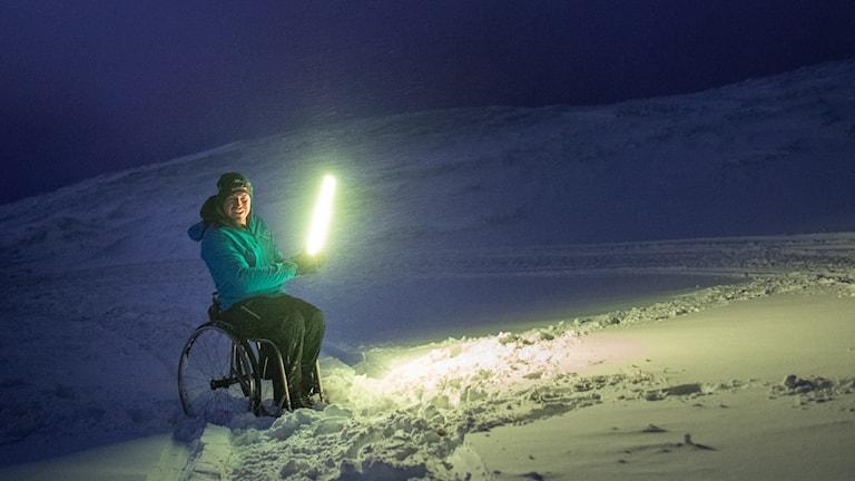 På fotot syns en man i blå mössa och blå jacka i en rullstol. Han omges av ett kulligt snölandskap och håller i en signallampa som lyser starkt grönt. Det är kväll och ljuset är dramatiskt.