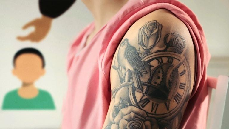 En mans tatuerade överarm. I bakgrunden håller en tecknad man handen över huvudet på en tecknad pojke.