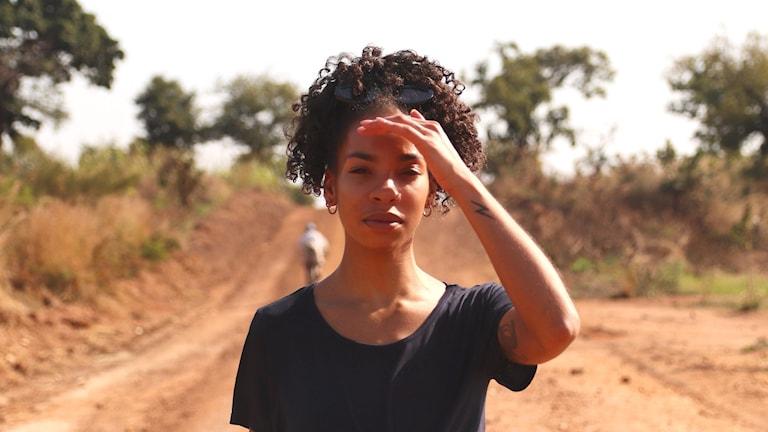 Bild på Janice som står på en enslig väg. Hon håller handen över ögonen för att skydda sig mot solen.