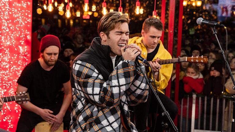 På fotot syns en ung man som sjunger intensivt i en mick. Bakom honom sitter en ung man gul jacka och spelar gitarr, och en annan bakom honom i röd mössa spelar på en trumlåda.