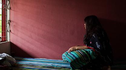 Ung bangladesisk kvinna vars ansikte inte går att se tittar åt vänster mot en fönster där solen strålar in.