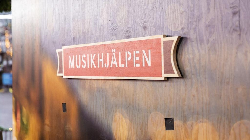 En bild på Musikhjälpen-skylten, gjord av trä inne i buren. Skylten sitter på en trävägg, och är formad som en banderoll i röd färg där det står Musikhjälpen i vit text.