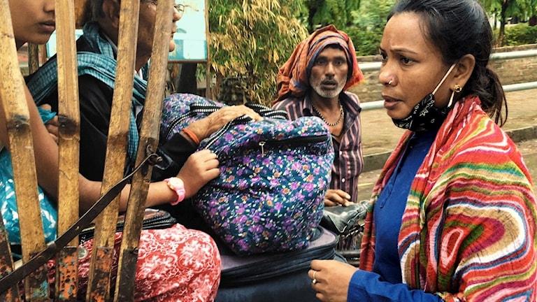 En kvinnlig gränsvakt mellan Indien och Nepal undersöker en förbipasserande vagn.