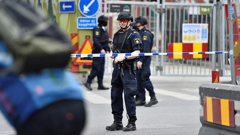 En beväpnad polis står bakom en avspärrning på en gata i Stockholm.