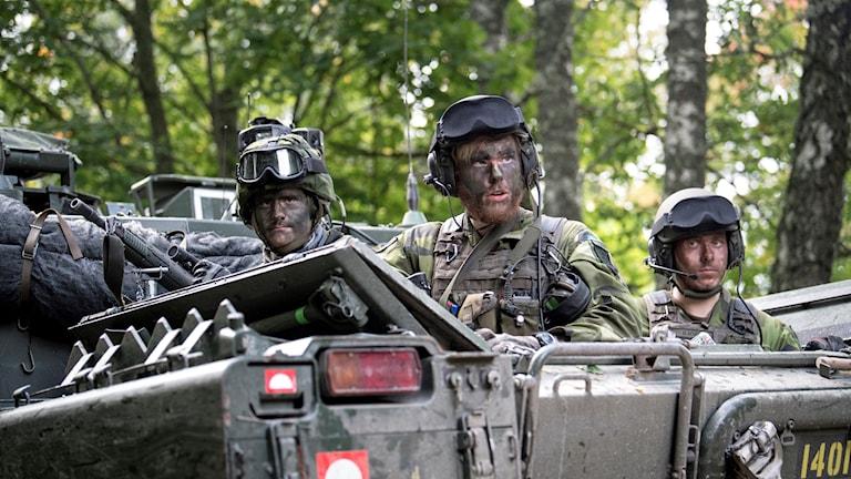 Tre militärer i kamouflagekläder sitter i en pansarvagn under en militärövning.