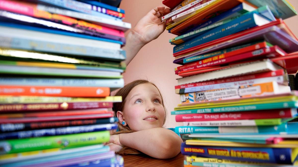En tjej sitter vid två högar med böcker och sträcker sig efter en i högen.