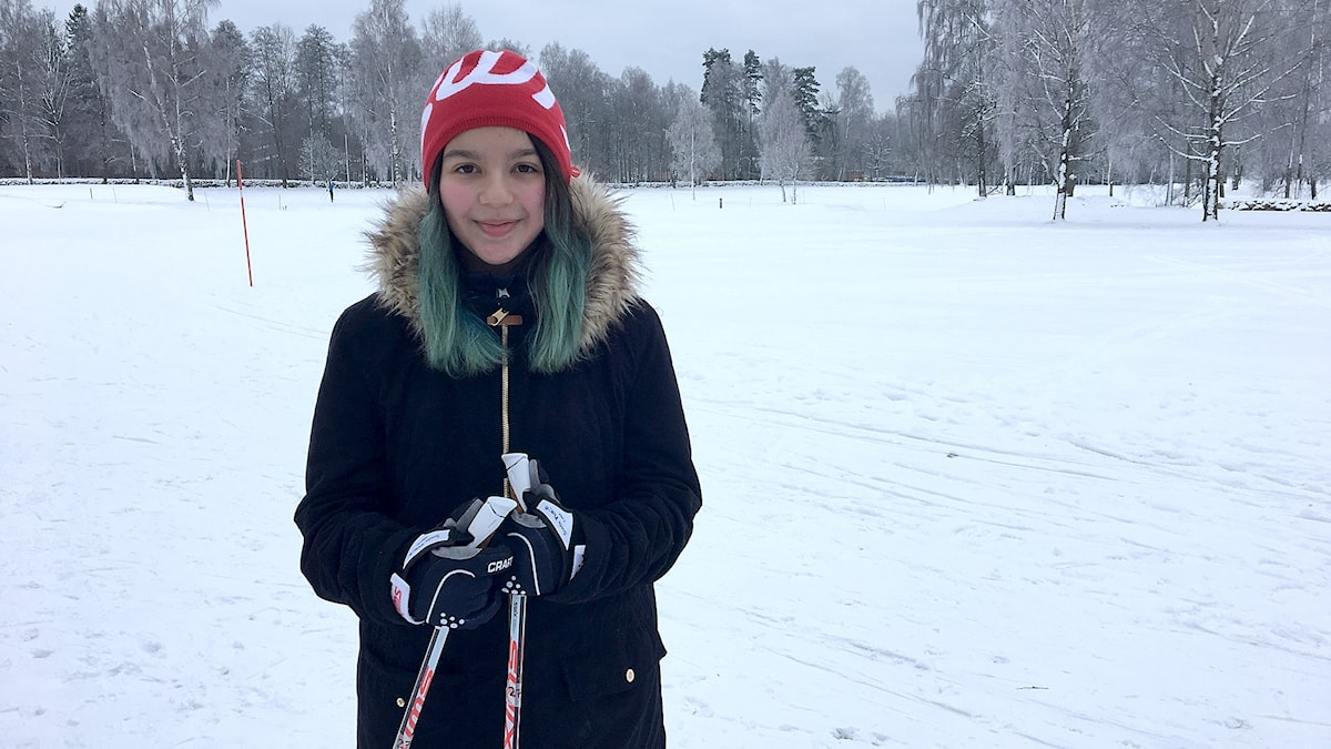 Marina Gavric står med skidorna på golfbanan.
