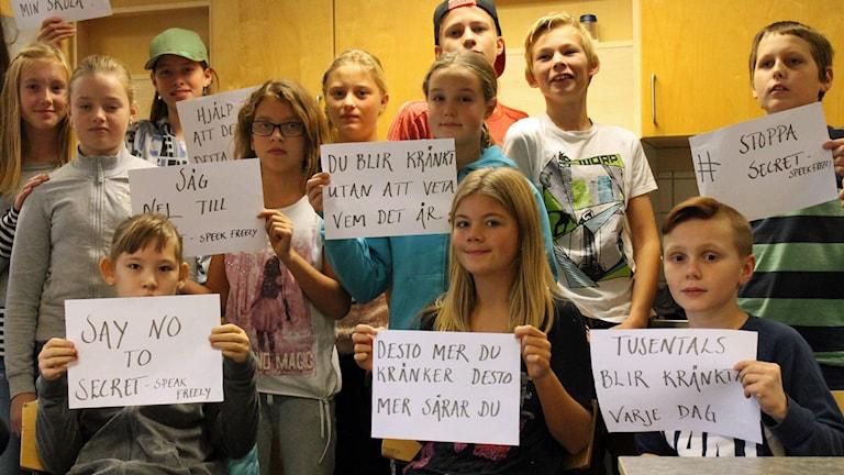 Klass 6 c på Frillesåsskolan håller upp lappar mot appen Secret. Foto: Anna Tigerström/Sveriges Radio