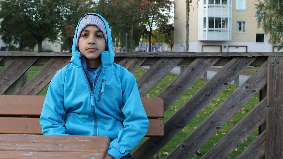 Ahmad Khaled har en ljusblå jacka på sig och en grå mössa. Han sitter på en bänk i ett bostadsområde.