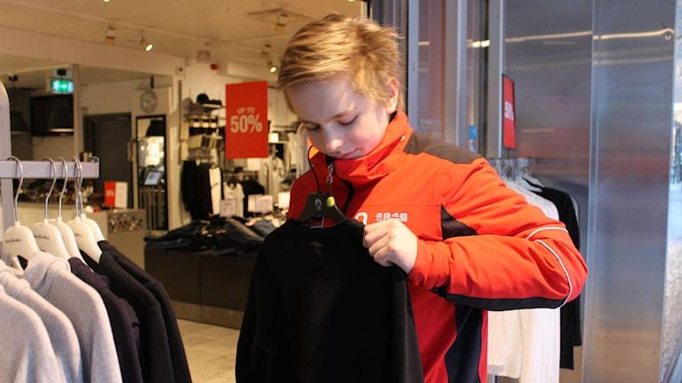 Albin Cronqvist står utanför en affär och håller upp en svart tröja. Foto: Anneli Koskinen/Sveriges Radio