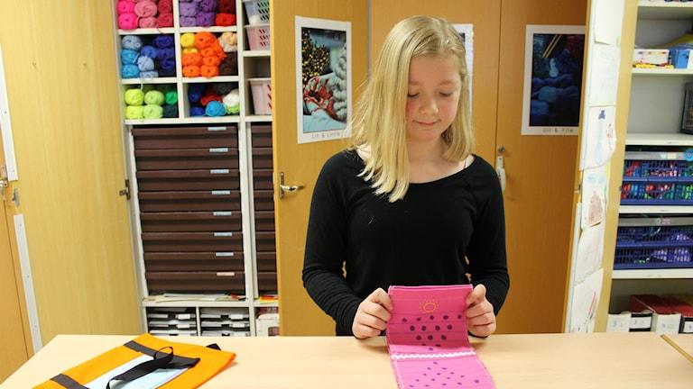 Sophia visar upp en rosa tygbit som hon sytt en spelplan av i syslöjden. Foto: Anneli Koskinen/Sveriges Radio
