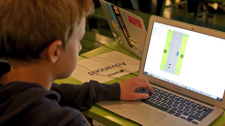 Isak sitter vid en dator och programerar.