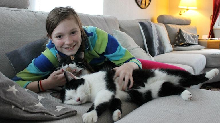 Här ser man Emilia i soffan med sina två katter.
