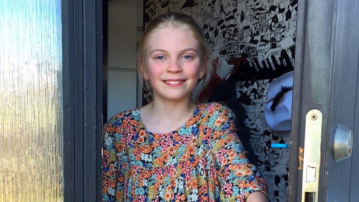 Swea Egerbo står i dörröppningen i en blommig klänning.