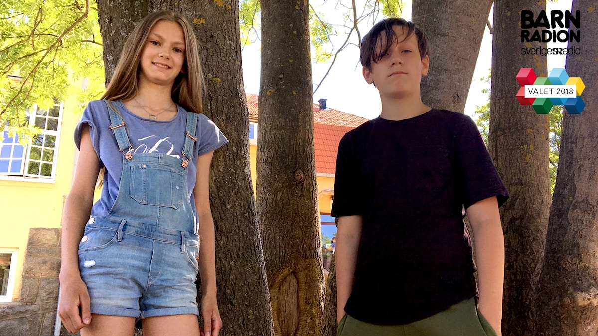 Alicia Birgmark Garcia och Max Mircovic står mot två träd på skolgården. I bakgrunden syns den gula skolbyggnaden.