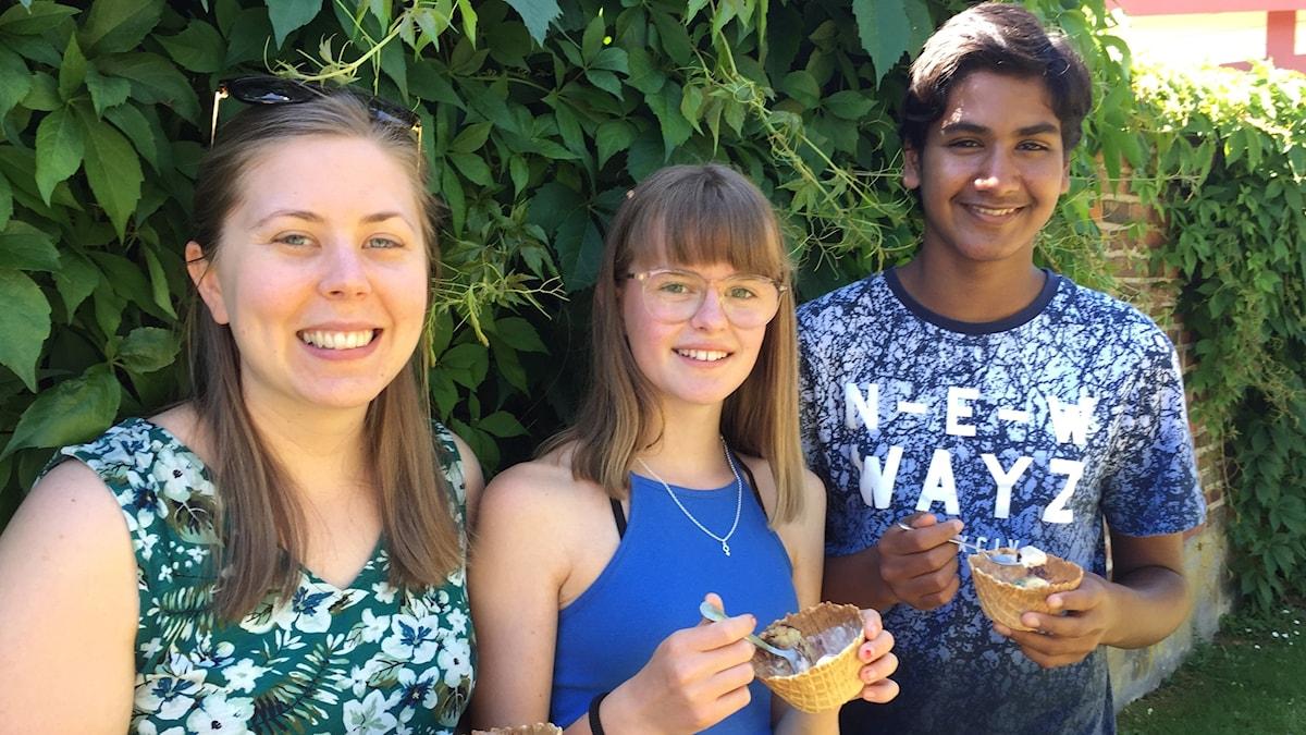 Anneli, Thea och Raghav står vid en grönskande buske och äter glass och ler in i kameran.