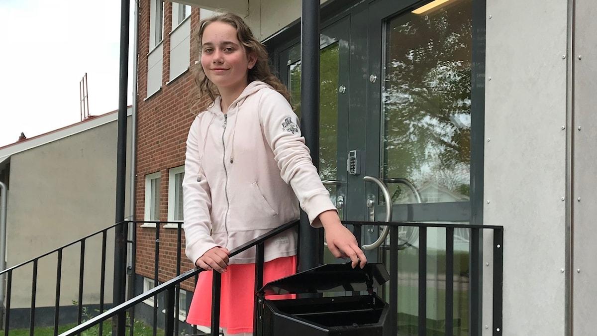 Julia står på en trappa och öppnar locket på en soptunna.