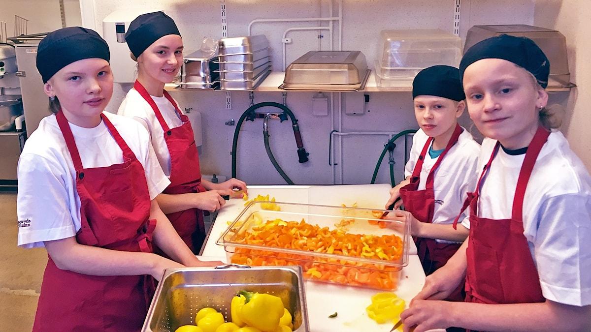 Ines Westhall, Maja Palmér, Noah Claweland Andersson och Tobias Holgersson hackar grönsaker i skolköket på Dackeskolan. Alla har fött förkläde och svart sjalett och hackar paprika och morötter.