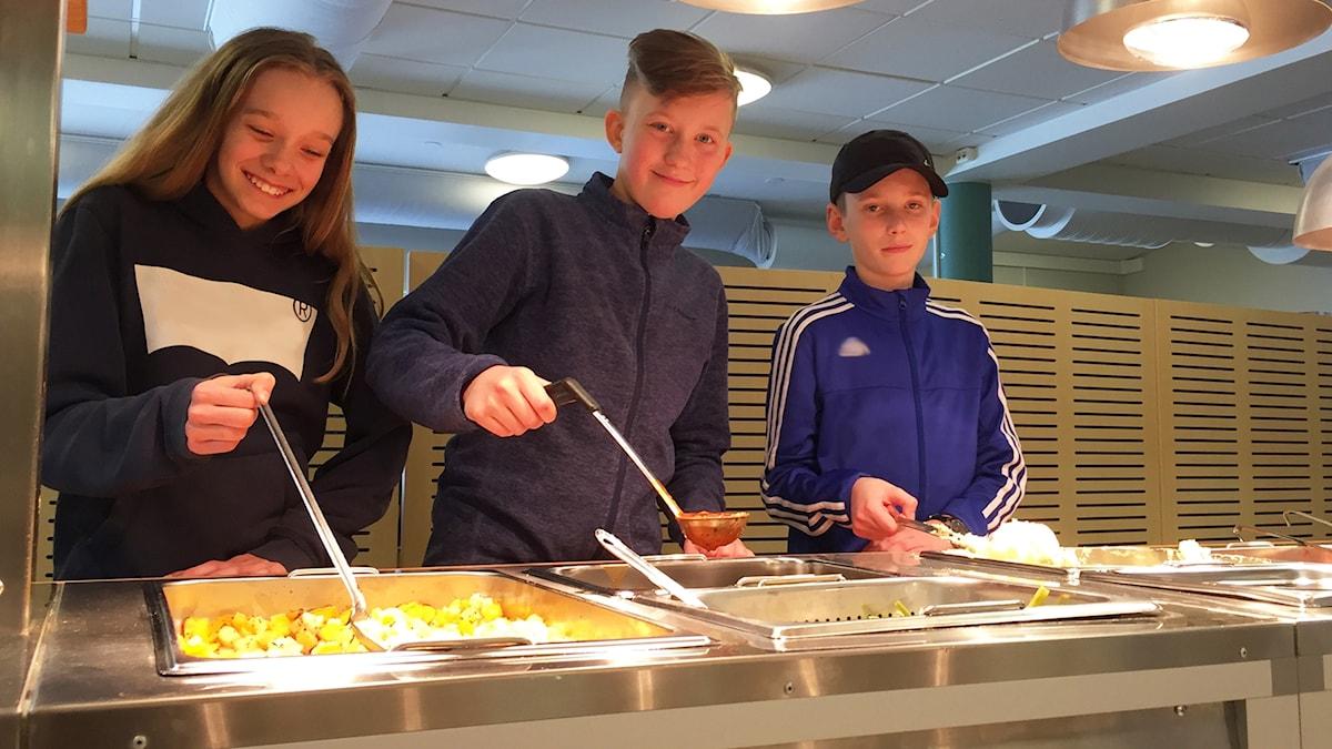 Tess, William och Lucas tar mat i matsalen.