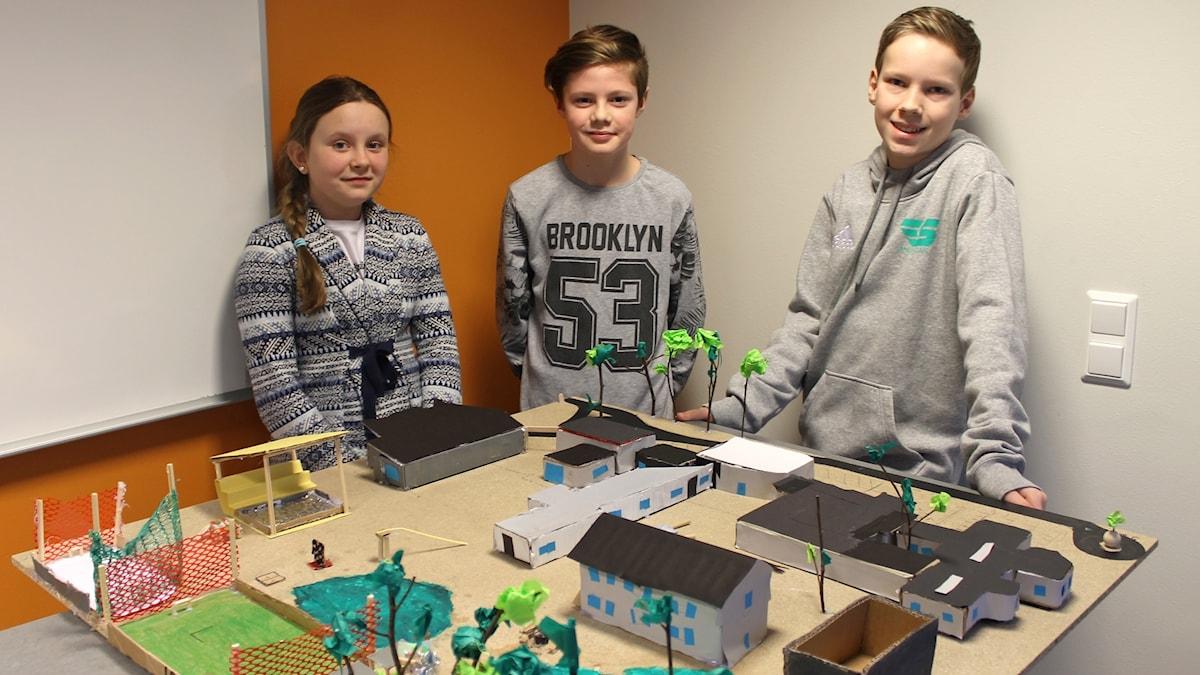 Maja Jakobsson, Gustav Björnsson och Anton Tour står bakom en modell av skolan. På modellen syns bland annat en isrink, en konstgräsplan, massa skolbyggnader, skog och en gul scen.