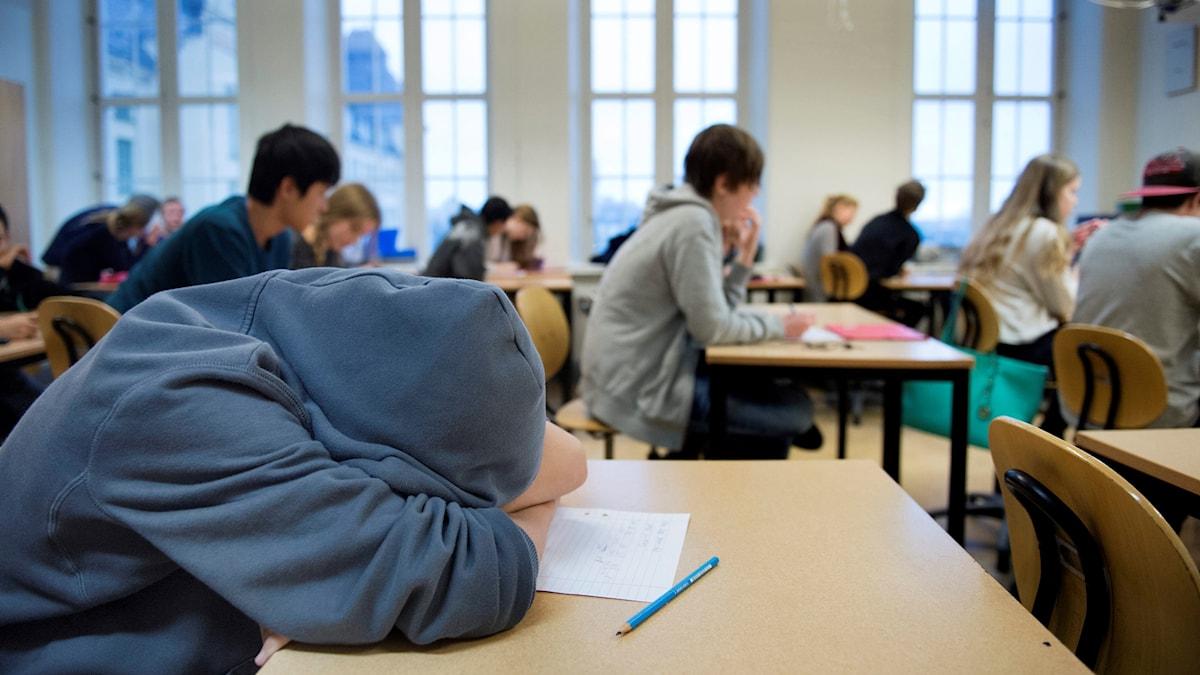 En elev lutar huvudet mot bänken i klassrummet.