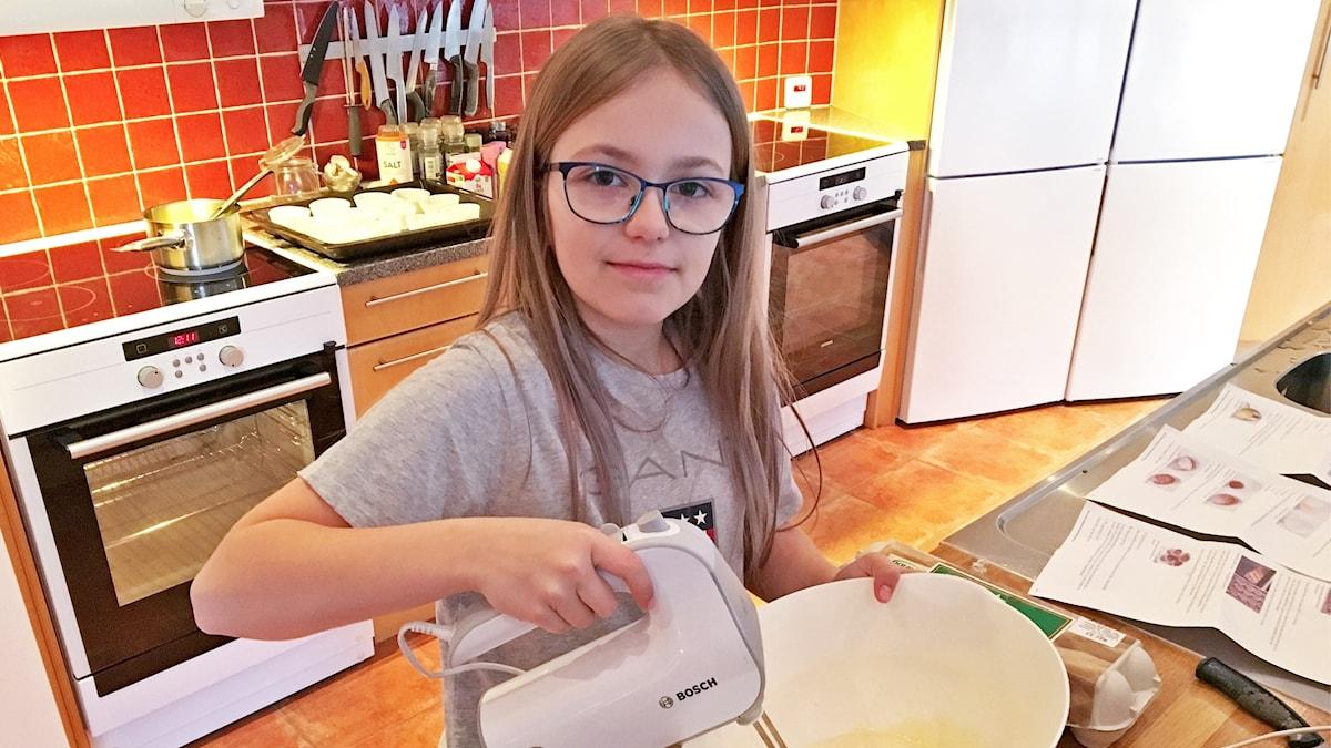 Moa Lindstrand står i ett kök och vispar kaksmet