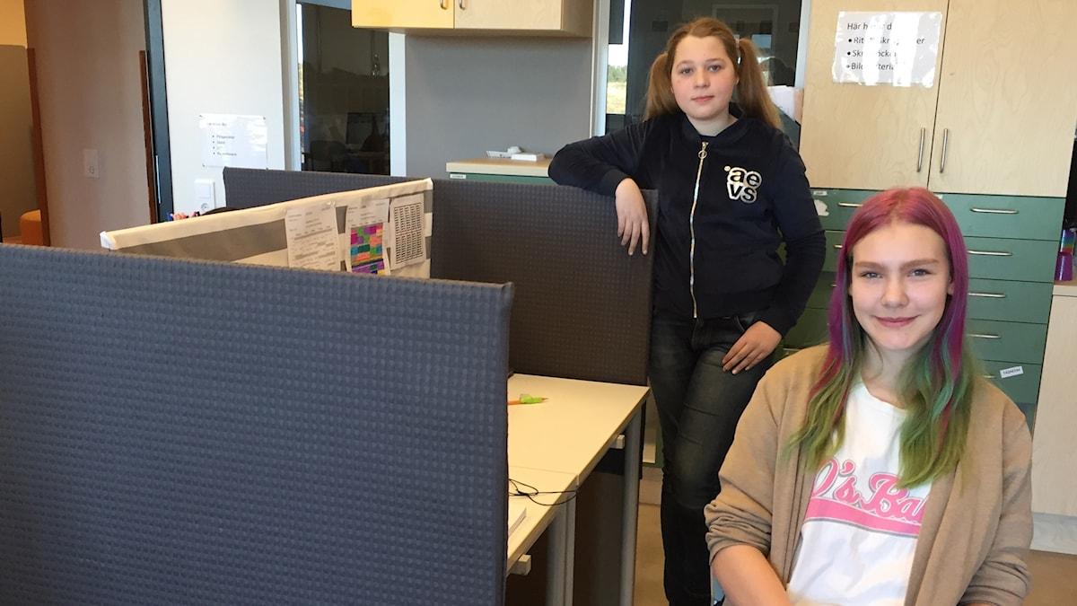 Swea och Filippa bredvid ett av skrivborden med tygskärmar.