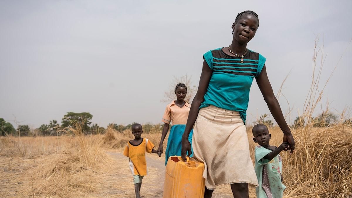 En kvinna och barn bär vatten i dunkar.