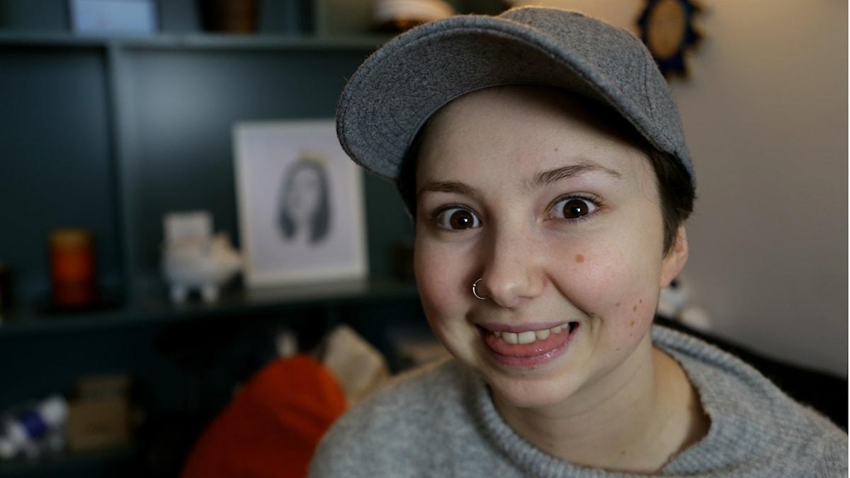 Porträttbild på Lovisa Karlsson som ler och sträcker ut tungan lite.