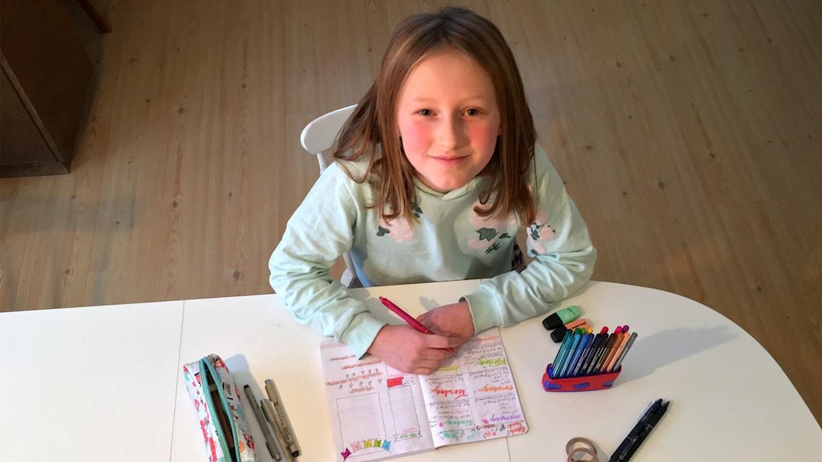 En tjej som sitter vid ett bord och målar i en anteckningsbok. Tittar upp in i kameran.