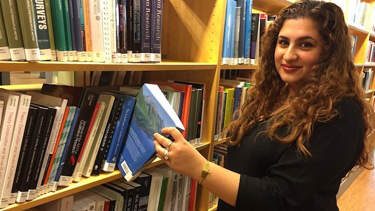 Hiba Weli står vid en bokhylla och lyfter ut en bok.