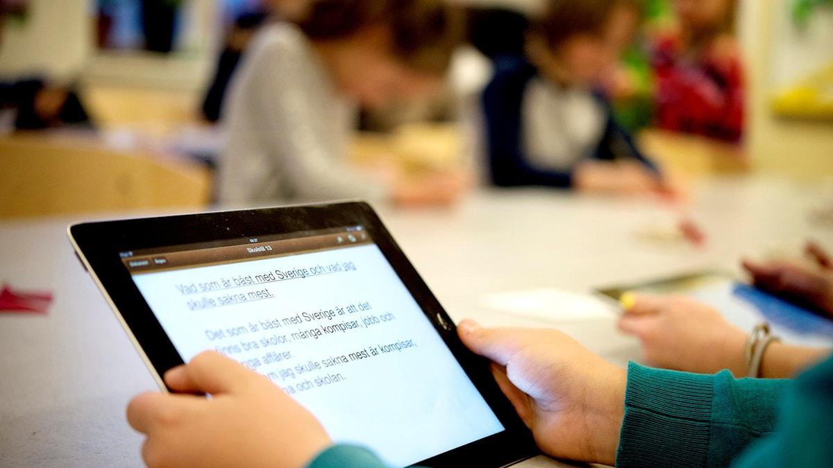 Ett barn håller i en läsplatta. I bakgrunden syns andra barn sitta och skriva.