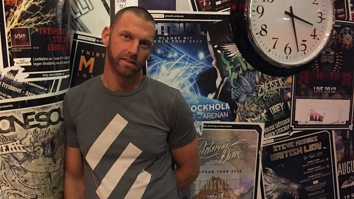 Peter Svensson står mot en vägg fylld med affischer och en klocka.
