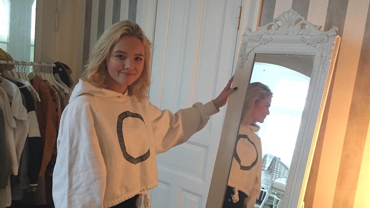 Malou Prytz står framför sin vita spegel.